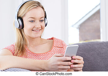 Woman Streams Music From Mobile Phone To Wireless Headphones