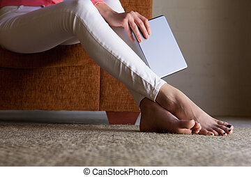 Woman feet on floor at home with digital tablet