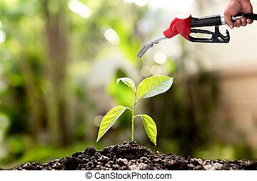 Environment concept saving hand holding fuel nozzle over new life plant