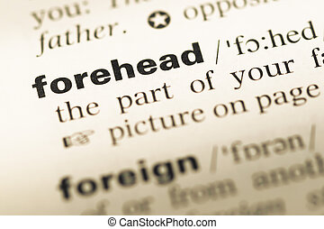 Close up of old English dictionary page with word forehead