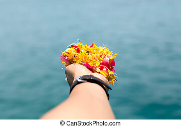 Human hands holding colorful flower
