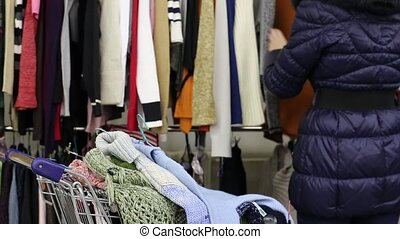 Girl Choosing Clothes And Putting To The Cart