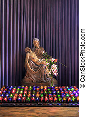 The Pieta Sculpture Altar with Colorful Lit Candles