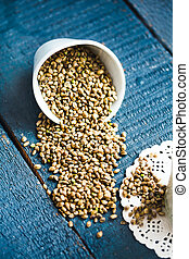 Whole hemp seeds in a white bowl, placer, blue background,...