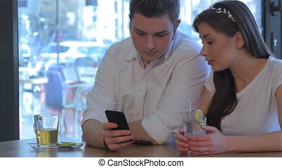 Woman laughs looking at the man's phone - Pretty caucasian...