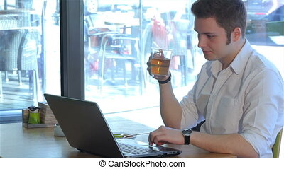 Man uses laptop at the cafe - Brunette man using laptop at...