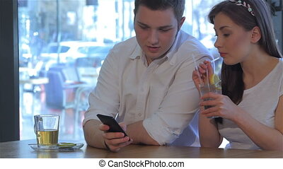 Woman drinks cocktail near the man at the cafe