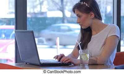Woman uses laptop touchpad at the cafe - Beautiful brunette...