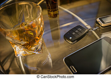 Glass of alcoholic drink and car key, on the table, light background