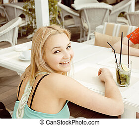 portrait of two pretty modern girl friends in cafe open air...