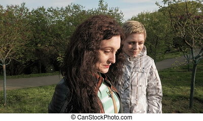 Two smiley girls friends talking in a green park - Two...