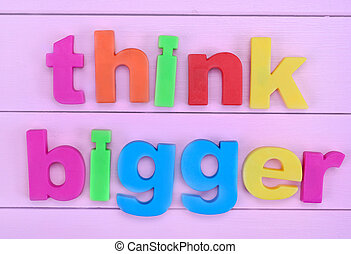 Words Think Bigger on pink table - Words Think Bigger on...