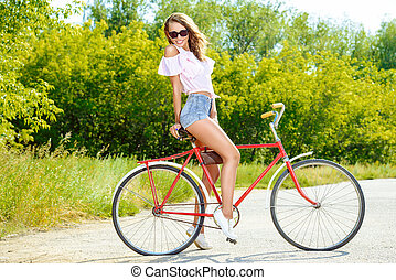 happy holidays - Happy girl riding a bicycle in the park on...