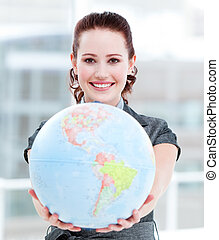 Charismatic businesswoman holding a terrestrial globe in the...