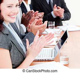 Cheerful business people applauding a good presentation in...