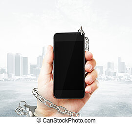 Smartphone cuffed to hand - Smartphone with blank screen...