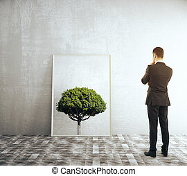 Framed tree picture - Businessman looking at a framed...