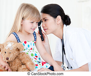 Asian doctor examining little girl with medical equipment...