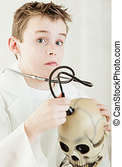 Surprised boy checking skull with stethoscope - Surprised...