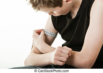 Boy flexing bicep and measuring arm - Close up of male youth...