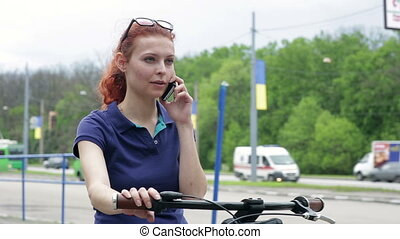Young woman on bike in park talking on cell phone - Young...