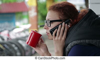 Beautiful woman drink coffee and call phone