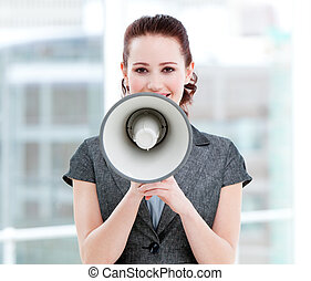Confident businesswoman yelling through a megaphone standing...