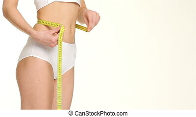 Woman measures her waist - Close up of slim woman measuring...