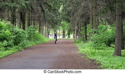 Woman riding a bike through a green forest