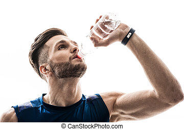 Attractive male athlete drinks fresh liquid - Waist up...