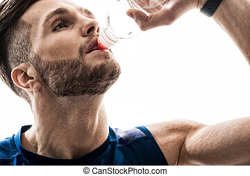 Cheerful thirsty sportsman drinking water from bottle -...