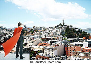 Businessman with red superhero cape standing on pedestal and...