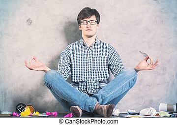 Meditating man - Handsome caucasian man meditating on messy...