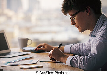 Man using calculator and writing - Businessman using...
