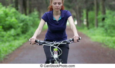 Woman use of the smart phone and riding a bike