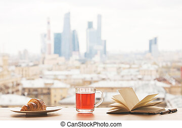 Open book and tea - Desktop with cup of tea, croissant on...