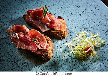 Two slice of Spanish tapas with jamon on a wooden table