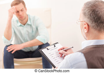 Mature psychotherapist is giving advice to patient -...