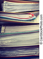 Piles of binders with documents.