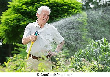 Gardener watering the plants using a rubber hose
