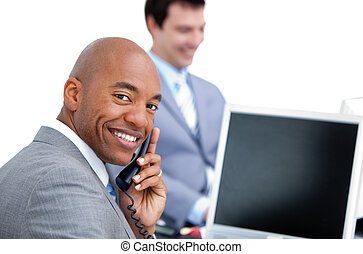 Happy businessman on phone and his colleague working at a computer in the office