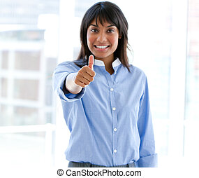 Happy female executive with a thumb up standing in the...