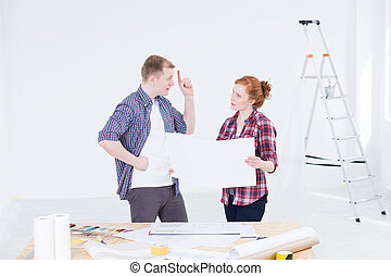Persuading her to his design ideas - Young man and woman in...