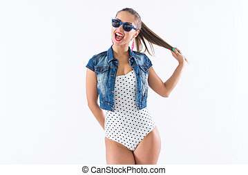 Studio shot of a young happy girl laughing, holding her...