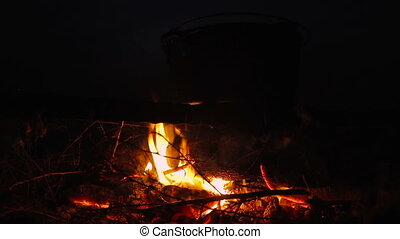 Cooking meal in cauldron on burning campfire at night