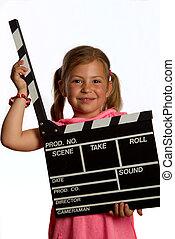 Pretty young girl holding a clapperboard in the open...