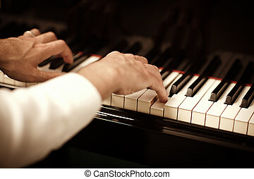 man playing piano - close up of male hands playing piano....