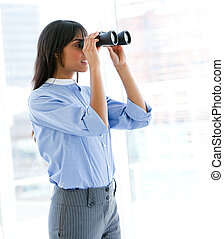 Confident female executive looking through binoculars in the...