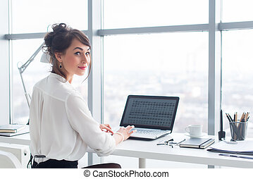 Attractive businesswoman working at office using pc,...