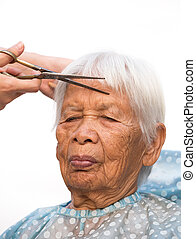 cutting senior woman's gray hair - Hair stylist cutting...